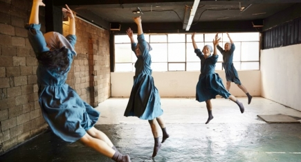 Four dancers jumping in an open space wearing blue dresses