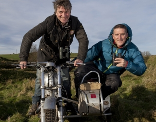 TV presenters Martin Hughes-Games and Iolo Williams on a motorbike and side-car driving through a muddy field