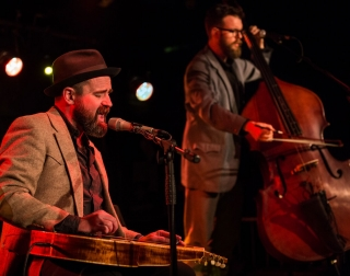 Martin Harley and Daniel Kimbro performing on stage with a double bass and slide guitar