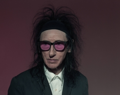 John Cooper Clarke wearing purple tinted, black rimmed glasses