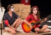 Actresses sit on the stage floor singing, one holds a guitar. Their faces are painted