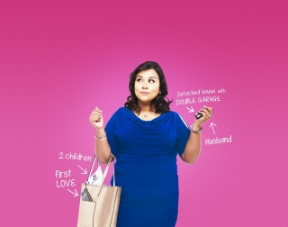 An Indian actress in a blue dress standing in front of a pink background
