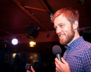 Comedian Alun Cochrane with a microphone on stage