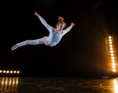 A dancer dressed in white, jumps (in a star shape) across the stage