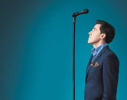 Comedian Rob Brydon in a suit standing beneath a microphone