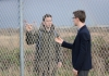 To men stand either side of a wire fence - boarder crossing - looking at one another