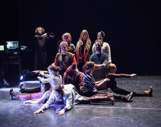 A group of young adults on stage all wearing wooly jumpers