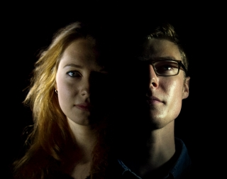 A half-lit portrait of young man and a young woman.