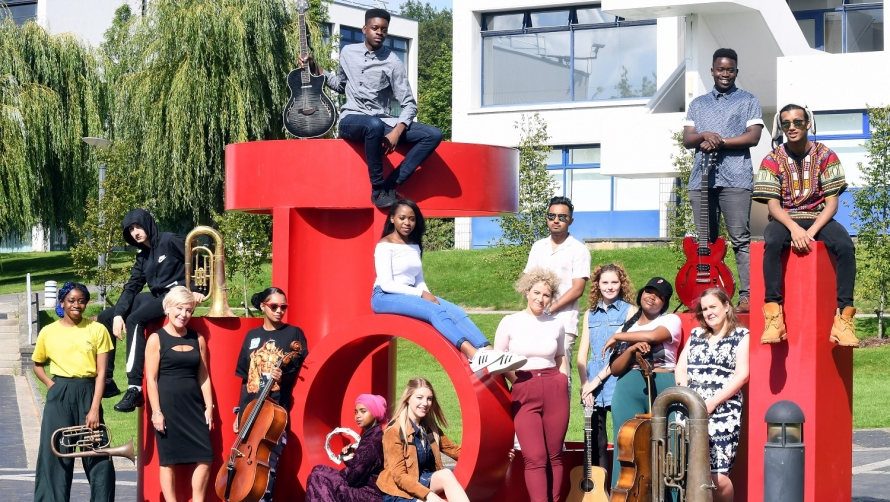 12 young musicians from Coventry pose with their musical instruments