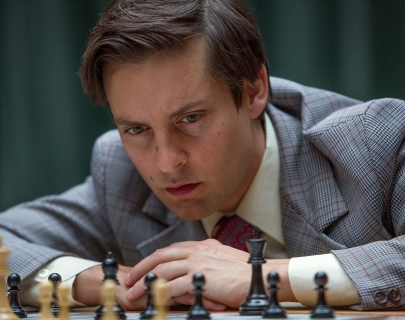 Actor Tobey Maguire dressed in a light blue suit hunched over a chess board