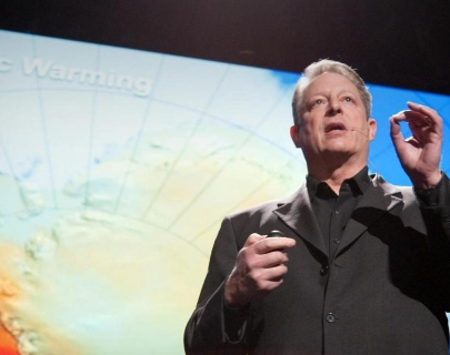 Al Gore on stage, in front of a big screen, presenting to an audience.