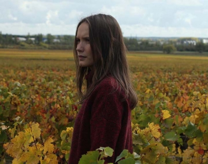 A woman with long hair standing in a field
