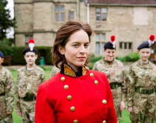 Woman in a red military coat standing infront of soldiers