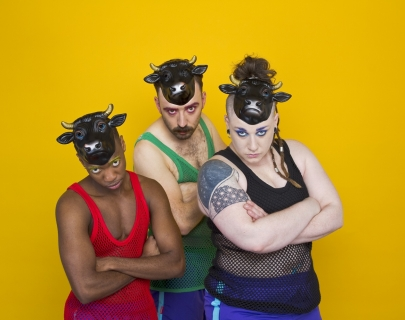 Three actors, standing in front of a yellow background, dressed in punk gar and with plastic black cows masks on their heads