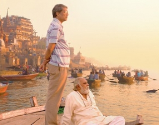 Two men stand on a boat looking out with more boats and ancient buildings behind them.