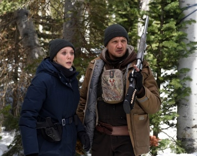 FBI Agent Jane Banner (Elizabeth Olsen) and hunter Cory Lambert (Jeremy Renner) in a snowy forest.