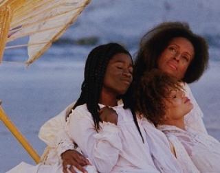 Three women sit on a beach in white dresses underneath a broken wooden umbrella.