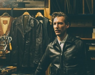 Laaksonen (Strang), a man wearing a black leather jacket stands in a shop, with more jackets behind him.