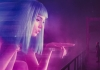 Blade Runner Officer K (Gosling) looks at a huge, digital protection of a woman with blue hair.