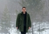 Investigator Harry Hole (Fassbender) walks in the snow, carrying a gun.