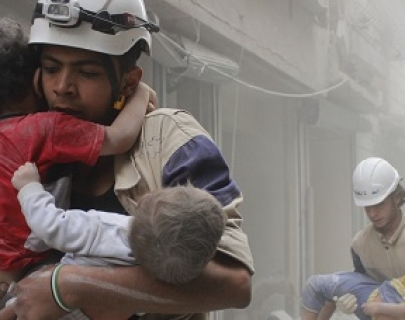 Men in hard hats and protective clothing carry injured children through a war zone.