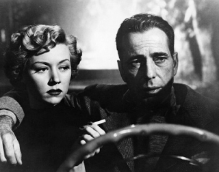A woman smokes a cigarette in an open top car, driven by a man with short hair. Black and white.