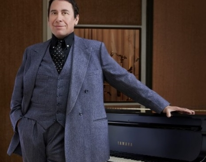 Jools Holland in a blue suit leaning against a piano