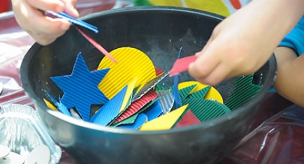 A child's hands playing with craft materials in a bowl