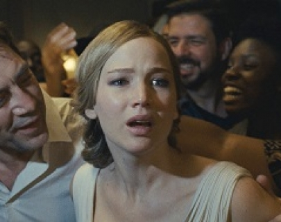 Actress Jennifer Lawrence in a white dress trying to escape from a crowd of people as actor Javier Bardem smiles.