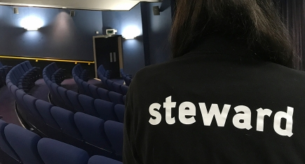 the back of a Stewards T shirt, in the cinema