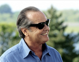 Jack Nicholson in a blue shirt an black sunglasses, on an outdoor background