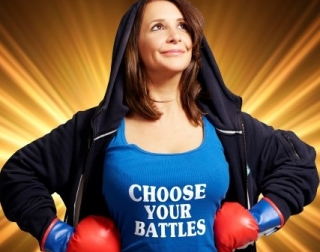 Lucy Porter dressed as a boxer, wearing a t-shirt with the words Choose Your Battles