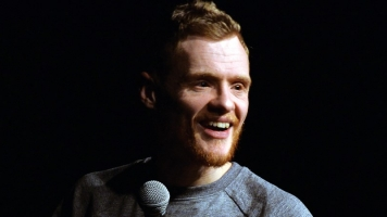 Comedian Andrew Lawrence holding a mic on a black background