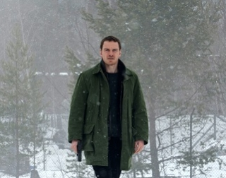 Actor Micheal Fassbender walking through a snowy wood