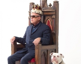 Suggs sitting on a throne wearing a crown with a dog on his side