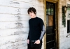 Singer Jake Bugg wearing a black outfit standing outside a house