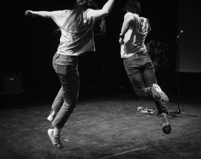 Two actors in black and white jumping