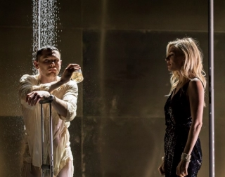 Actor Jack O'Connell holding a whiskey glass while being showered with water and talking to actress Sienna Miller