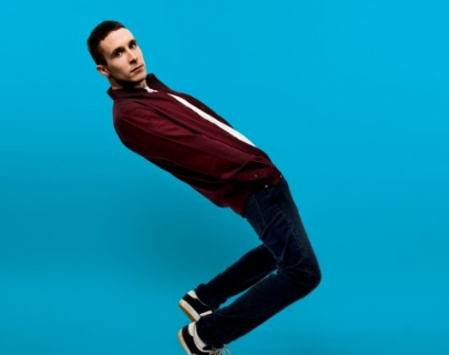 Larry Dean wearing casual clothes leaning back on a blue background