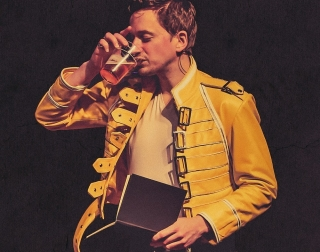 John Robins dressed in a yellow leather jacket, holding an open book and drinking a pint of beer