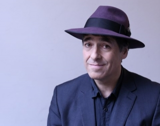 Comedian Mark Steel wearing a blue suit and a hat