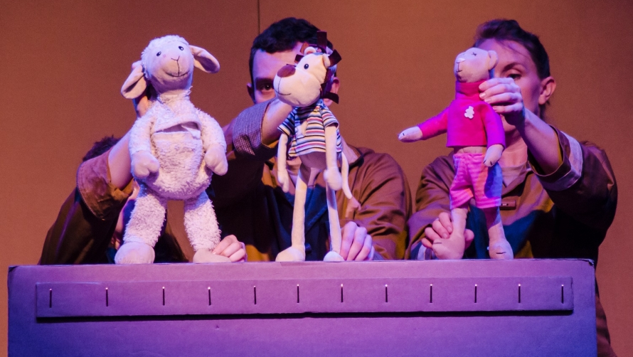 toys on top of a cardboard box being controlled like puppets by actors on stage