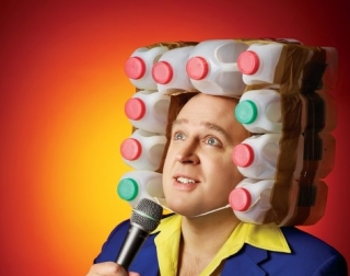 Comedian Tim Vine wearing a hat made of milk bottles and a blue suit