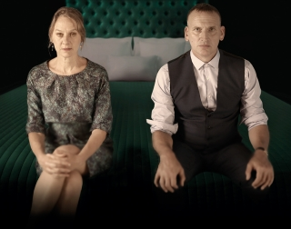 Actors Christopher Eccleston and Niamh Cusack sitting on a bed both wearing dark elegant clothes