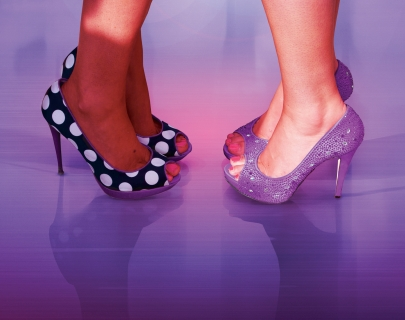 Close up of two people's feet wearing high heels