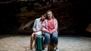Actresses Taj Atwell (Rita) and Gemma Dobson (Sue) sitting on two chairs on the stage set of Rita, Sue and Bob Too