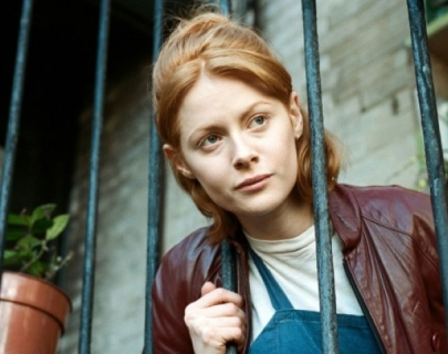 Daphne wearing a Burgundy leather jacket putting head between green bars