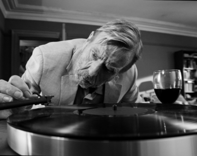 Black and white picture of actor Timothy Spall putting a record on a gramophone