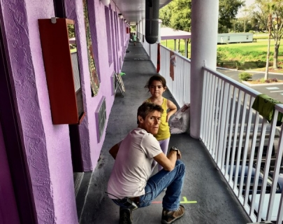 Bobby (Dafoe), a middle-aged man in a white t-shirt and blue jeans, looks over his shoulder as he kneels in front of a small girl in a yellow top, on a purple motel balcony.