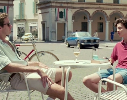 Two young men wearing summer clothes and sitting down at a table in a piazza